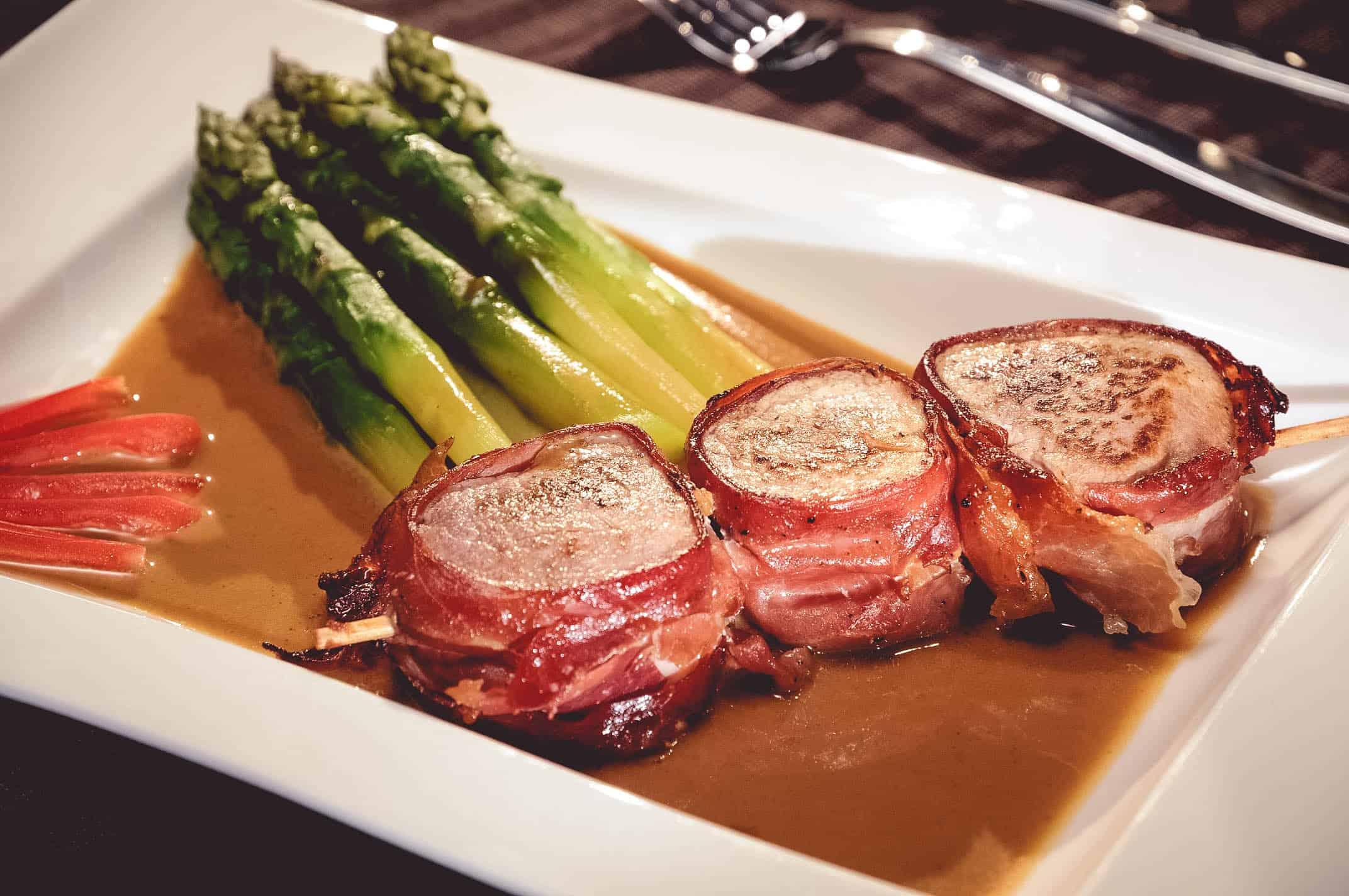 Brochette de filet de porc enrobé de jambon, fricassée d'asperges et jus de veau